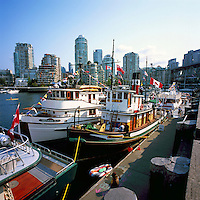 Vancouver, BC, British Columbia, Canada - Historic Wooden Boats docked in False Creek at Granville Island, Yaletown Highrises in background