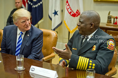 United States President Donald J. Trump speaks with Fire Chief Joel Baker, Atlanta Fire Rescue Department as he meets with the I-85 bridge first responders in the Roosevelt Room of the White House in Washington, DC on Thursday, April 13, 2017.<br /> Credit: Ron Sachs / Pool via CNP