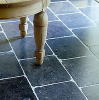 Close up of the leg of an antique Belgian round table against bluestone flooring in the entrance hall
