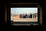Young Iraqi schoolgirls wait outside their rural school as seen from the window of a passing U.S. Army Humvee, March 12, 2008