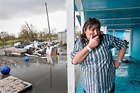 Susie Danos stands on the porch of her house after hurricane Gustav delivered wide spread wind damage and water damage to the predominantly Native American community of Isle Jean Charles, Louisiana. The island remained without electricity and running water for weeks. Residents were under mandatory evacuation before the storm and many are relying on emergency food, ice and water supplies in the sweltering summer heat.