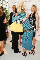 Betsey Johnson hugs Andrea Goldsmith, who won a trip to Paris during the charity raffle at the CURVE and CFDA Party For A Cause event during the CURVENY Lingerie & Swim show, at the Jacob Javits Convention Center, August 2, 2010.