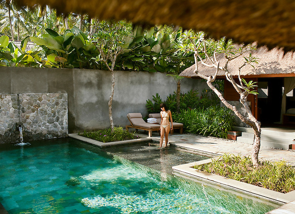 Woman entering pool of Bile Deluxe Pool Villa, a private pool villa at Kayumanis Ubud, Bali, Indonesia.
