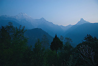 Five peaks of the Annapurna range are visible as shadows against the soft, blue, pre-dawn sky in Nepal. To the right, the unmistakable silhouette of Machapuchare towers majestically over the Modi River valley