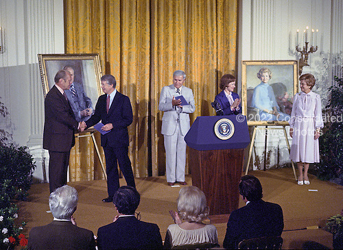 United States President Jimmy Carter shakes hands with former US President Gerald R. Ford as he and first lady Rosalynn Carter participate in the unveiling ceremony of the portraits of President Ford and former first lady Betty Ford in the East Room of the White House in Washington, DC on August 4, 1980. The paintings will be on permanent display at the White House along with those of other US Presidents and first ladys.  From left to right: President Ford; President Carter; Nash Castro, Vice Chairman, White House Historical Association; first lady Rosalynn Carter; and former first lady Betty Ford.<br /> Credit: Benjamin E. &quot;Gene&quot; Forte / CNP
