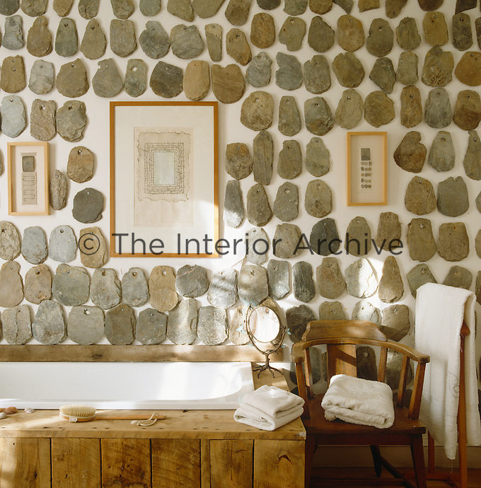Misshapen stone roof tiles adorn the wall of this rustic bathroom with a bath clad in rough pine planking
