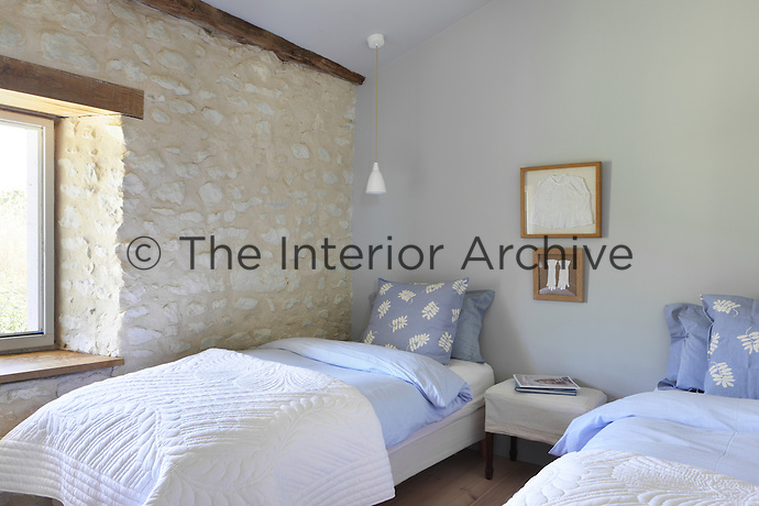A twin bedroom for guests, between them hangs framed vintage pieces of childrens clothing