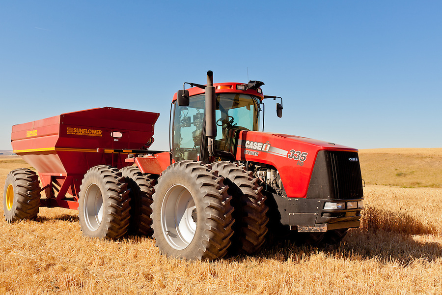 A Case 335 tractor and Sunflower grain trailer sit in a harvested wheat field.