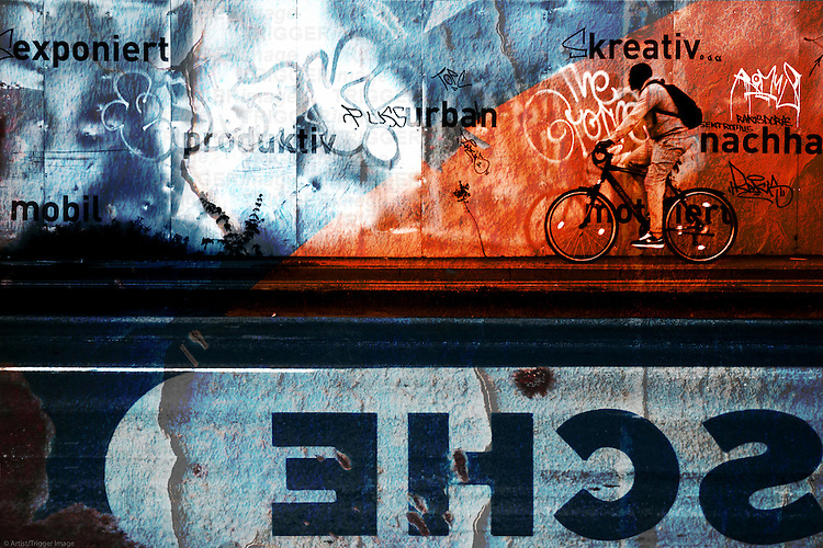 A black cyclist is passing a painted metal bulkhead which is painted with slogans and graffiti.