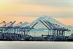 Cargo cranes and container ships in Port of Seattle, with Mt. Rainier behind.