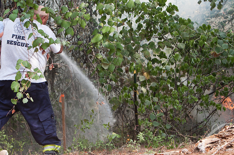 An firefighter from the Iola Volunteer Fire Department works to douse the flames along Sparks  Lane in Grimes County, Texas.  The Dyer Mill fire has now consumed over 5800 acres.