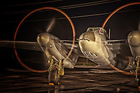 An up close view at night of the de Havilland Mosquito with it's engines started on the tarmac at the Canadian Warplane Heritage Museum.