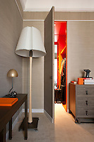 A concealed door in the fabric-lined walls of the master bedroom opens to reveal a walk-in wardrobe