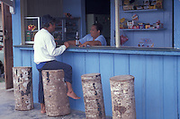 Man chatting at an outdoor food stall in the town of Bocas del Toro, Isla Colon, Panama