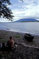 Tourist sitting on a beach, Isla de Ometepe, Nicaragua
