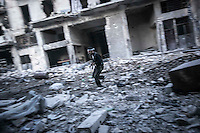 In this Thursday, Nov. 01, 2012 photo, a rebel fighter runs for cover through a street at the front line during clashes in the nearby Karmal Jabl battlefield in Aleppo, the Syrian's largest city. (AP Photo/Narciso Contreras).