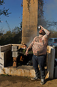 Charleston, South Carolina<br /> October 26, 2013<br /> <br /> Matthew Matheson, who goes by &quot;Matty Death Bro&quot; on social media due in part to the heart attack he suffered in his mid-20&rsquo;s downs a beer as the chefs burn off the excess barbecued pig heads. <br /> <br /> Internationally renowned chefs, attending the Cook It Raw.barbecue at Bowens Island.