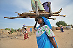 Women carry firewood and other supplies on their heads in the Goz Amer refugee camp in eastern Chad. More than a quarter million residents of Darfur live in camps in Chad, along with almost 200,000 Chadians who have been internally displaced by related violence.
