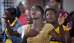 A woman and other worshippers sing in an evangelical church in La Hoya, a small rural town near Barahona in the southwest of the Dominican Republic. The service brings together Dominicans and Haitian-Dominicans from a nearby batey in an unusual demonstration of unity in a land where discrimination against Dominicans of Haitian ancestry is growing.