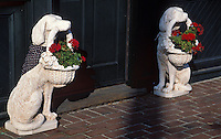 Two ceramic dog figurine flower pot holders outside entrance.