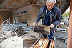 Naoto Matsumura cleans out hives of bees that have died in the government-imposed no-go zone about 10 km from the Fukushima Daiichi Nuclear Power Plant in Tomioka, Fukushima  Prefecture, Japan on 01 Mar. 2012. The hives recorded high readings of radioactive cesium..Photographer: Robert Gilhooly
