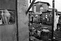 Philippines. National Capital Region. Manila. Paradise village. A man carries on his shoulders clean potable water in metal buckets. Drinking water or potable water is water pure enough to be consumed or used with low risk of immediate or long term harm. An advertising and a calendar for Boss cigarettes with the body of a woman wearing a bikini is taped on the wooden wall. A laundry with clean clothes is hanging on a rope and drying in the sun. Paradise village has a population of 15'000 people and is a part of Barangay Tonsuya situated on Lettre Road in Malabon. Manila is part of the National Capital Region (NCR) on Luzon island. Manila is the capital of the Philippines and one of the sixteen cities that comprise Metro Manila. Metro Manila is the most populous metropolitan area in the Philippines. © 1999 Didier Ruef