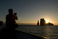 Tourists to the Galápagos Islands photograph Kicker Rock. These two vertical rocks, located of the coast of San Cristóbal, are the remains of an ancient lava cone that has been eroded by the sea and rise 500 feet above the ocean..