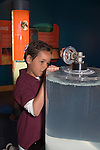 Oakland CA 2nd grade boy on school field trip to Chabot Space and Science Center manipulating a crank to create a vortex