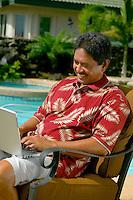 Local man in aloha shirt on laptop computer near pool outdoors.
