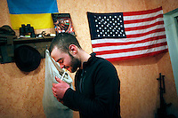 """UKRAINE, 02.2016, Novohrodivka, Oblast Donetsk. Ukrainian-Russian conflict concerning Eastern Ukraine / Foreign volunteers (""""Task Force Pluto"""") fighting with the far-right militia Pravyi Sektor against the Russian-backed separatists: Cowboy (USA) lights a good-morning cigarette in front of the Ukrainian and the US flag. © Timo Vogt/EST&OST"""