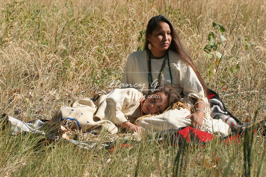 Native American Sioux Indian Women and child sitting on a blanket in the long grass