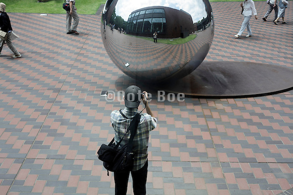 person making a selfie with the help of a mirroring artwork