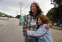 Camp Hope, eine Zeltstadt fuer Obdachlose in Ontario, Kalifornien.Bewohner David Busch und Freundin..Fotos © Stefan Falke..Camp Hope, a  tent city for the homeless in Ontario, California.Resident David Busch and friend, wearing a  'MORE LOVE' sign