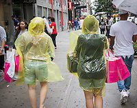 Rain protected shoppers with their Victoria's Secret shopping bags in Herald Square in New York on Independence Day, Friday, July, 4, 2014. Many stores remained open and offered discounts for the holiday.  While sales on other holidays might have better bargains, the Fourth of July offers the unique opportunity to purchase merchandise while it is still in season as retailers prepare to move it out for the back-to-school specials.  (© Richard B. Levine)