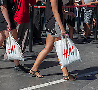 Visitors to Times Square in New York with their H&M purchases on Thursday, September 15, 2016.  U.S. retail sales for August were below analysts' expectations as automobile and gasoline sales were weak and shoppers abandoned their spending spree from the spring.  (© Richard B. Levine)