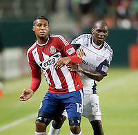 Chivas defender Dario Delgado (12) battles Revolution midfielder Kheli Dube (11) for position during the first half of the game between Chivas USA and the New England Revolution at the Home Depot Center in Carson, CA, on September 10, 2010. Chivas USA 2, New England Revolution 0.