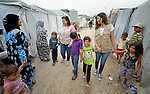 Rana Hage and Dominique Anid, both staff of International Orthodox Christian Charities, walk with children in a settlement of Syrian refugees in Minyara, a village in the Akkar district of northern Lebanon. Lebanon hosts some 1.5 million refugees from Syria, yet allows no large camps to be established. So refugees have moved into poor neighborhoods or established small informal settlements in border areas. International Orthodox Christian Charities, a member of the ACT Alliance, provides support for families in this settlement.