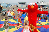 "Santa Monica Pier legend Michael Cladis dressed as Elmo dances with children at the Santa Monica Pier during the kicks off  Concert Series ""Wake Up With The Waves"" on Saturday, September 10, 2011. The children's interactive concert series are held every Saturday morning through October 29, 2011"