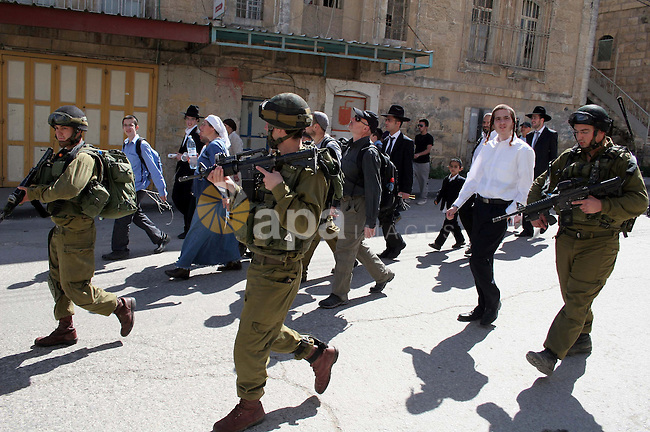Israeli soldiers escort Jewish settlers as they head to visit the tomb of Atnaeil Ben Kinaz in the occupied West Bank city of Hebron on March 31, 2010. The United States wants a four-month Israeli building freeze in occupied east Jerusalem, one several US demands aimed at reigniting dormant peace talks, media reports said. Photo by Najeh Hashlamoun