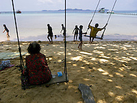 Thailand. Trat province. Ko Rang island. A woman seats on a swing and eats a thai lunch. Plastic bottle of water. A group of children play on another swing. Sand beach and clear water. Ko Rang island is a natural park. 13.04.09 © 2009 Didier Ruef