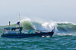 A Copper River commercial fisherman runs his boat through the dangerous surf of Strawberry Bar entrance enroute to his homeport of Cordova, Alaska from the fishing grounds at the mouth of the river in the Gulf of Alaska.