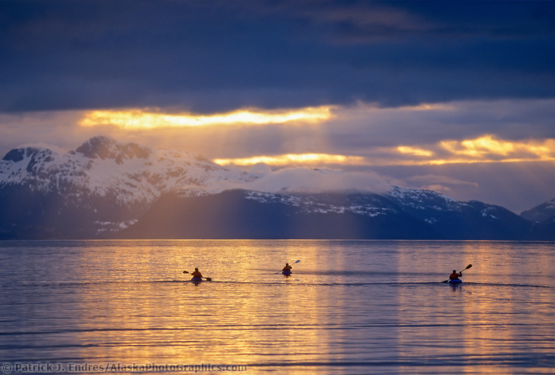 Sea kayakers paddle into the sunset, Prince William Sound, Alaska.