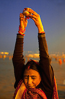India. Uttar Pradesh state. Allahabad. Maha Kumbh Mela. A woman offers water in a brass cup to the sun  in Sangam. Indian Hindu devotee pray at sunset. The Kumbh Mela, believed to be the largest religious gathering is held every 12 years on the banks of the 'Sangam'- the confluence of the holy rivers Ganga, Yamuna and the mythical Saraswati. In 2013, it is estimated that nearly 80 million devotees took a bath in the water of the holy river Ganges. The belief is that bathing and taking a holy dip will wash and free one from all the past sins, get salvation and paves the way for Moksha (meaning liberation from the cycle of Life, Death and Rebirth). Bathing in the holy waters of Ganga is believed to be most auspicious at the time of Kumbh Mela, because the water is charged with positive healing effects and enhanced with electromagnetic radiations of the Sun, Moon and Jupiter. The Maha (great) Kumbh Mela, which comes after 12 Purna Kumbh Mela, or 144 years, is always held at Allahabad. Uttar Pradesh (abbreviated U.P.) is a state located in northern India. 8.02.13 © 2013 Didier Ruef