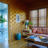 Gold and orange Chinese teapaper has been used to decorate the walls of the family room