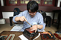 June 26, 2010 - Tokyo, Japan - A Japanese sword experts works on a long sword (katana) during The 1st Sword Craftsmen Exhibition of the NBSK (Nihon Bunka Shinko Kyokai) at Okura Musem of Art located in Okura Hotel in Tokyo, Japan, on June 26, 2010. The event runs from June 13 to July 25 and let sword masters show their skills such as sword polishing, sword fittings and mounting to visitors.