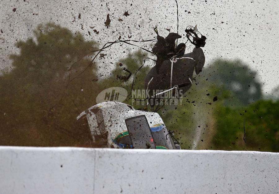 Apr 29, 2016; Baytown, TX, USA; Grass and dirt flies as NHRA pro mod driver Sidnei Frigo goes airborne and flips over the wall as he crashes during qualifying for the Spring Nationals at Royal Purple Raceway. Frigo was alert and transported via helicopter to a local hospital. Mandatory Credit: Mark J. Rebilas-USA TODAY Sports