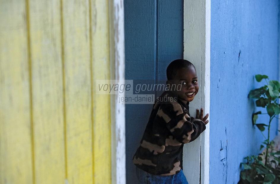 Les Bahamas /Ile d'Eleuthera/Harbour Island/Dunmore Town: enfant jouant devant les cabanons colorés du port