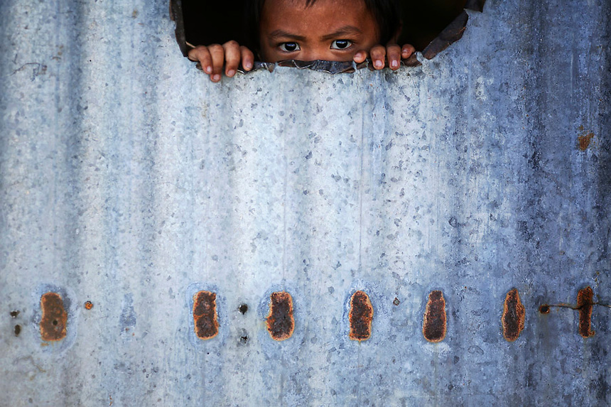 A child peers from inside a makeshift house with tin walls January 15, 2015 in the coastal part of Tacloban that was destroyed by Typhoon Haiyan. On his first visit to Asia's largest Catholic nation, Pope Francis will visit the central province of Leyte, which is still struggling to recover from Typhoon Haiyan that killed 6,300 people in 2013. About two million people are expected to attend an open-air mass on Saturday at Tacloban City airport, almost completely destroyed by Haiyan. REUTERS/Damir Sagolj (PHILIPPINES)