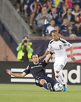 New England Revolution defender A.J. Soares (5) tackles Los Angeles Galaxy midfielder Paolo Cardozo (30). In a Major League Soccer (MLS) match, the Los Angeles Galaxy defeated the New England Revolution, 1-0, at Gillette Stadium on May 28, 2011.