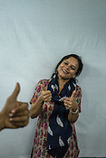 Runa Roka (54), founder of the Noida Deaf Society poses for a portrait with her students in the classroom of the foundation in NOIDA, India. <br /> Runa poses with a sign of appreciate while a student gives a thumbs up, which means appreciate in sign language.